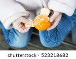 Small photo of Children peel a tangerine peel