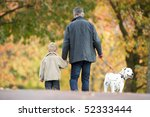 Stock photo man with young son walking dog through autumn park 52333444