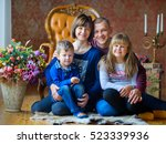 Small photo of Happy family sit and pose on a floor. Amicably embrace and smile. Strong family