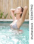 young woman relaxing in the pool | Shutterstock . vector #523447942