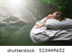 Small photo of A hidden place. Sleeping woman in deep forest lies on airbed