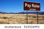 Small photo of Pay Raise road sign with blue sky and wilderness