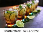 Stock photo glasses of cocktail with ice lime and mint on dark textured background 523570792