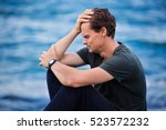 Small photo of Male adult puts hand on head and looks very distressed and is suffering from depression and intense sadness, he is crying and sitting by the ocean.