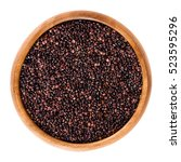 Small photo of Black quinoa seeds in wooden bowl. Edible fruits of the grain crop Chenopodium quinoa in the Amaranth family is a pseudocereal and used cooked. Isolated macro food photo close up from above on white.