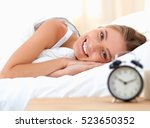 young sleeping woman and alarm... | Shutterstock . vector #523650352
