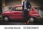 suited man posing next to a car | Shutterstock . vector #523824865