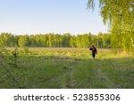 a man walks across the field to ...   Shutterstock . vector #523855306