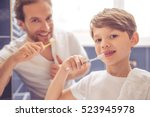 father and son are looking at... | Shutterstock . vector #523945978