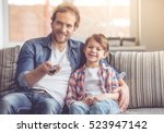 father and son are watching tv... | Shutterstock . vector #523947142