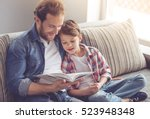 father and son are reading a... | Shutterstock . vector #523948348