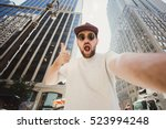 Happy funny bearded man taking selfie and showing thumbs up in Manhattan. Hipster tourist posing for photo while travel in New York. - stock photo