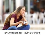 Stock photo sad girl waiting for a mobile phone call or message from her boyfriend sitting in a bench outside 524194495