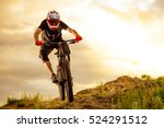Professional Cyclist Riding the Bike Down Rocky Hill at Sunset. Extreme Sport Concept. Space for Text. - stock photo