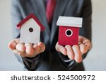 businessman holding two houses... | Shutterstock . vector #524500972
