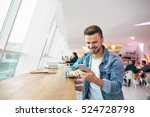 Stock photo man is sitting in front of the table near window he is looking at cellphone and chatting with 524728798