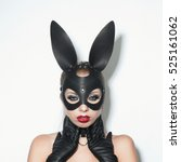 Small photo of Beautiful dominant blonde vamp mistress girl in leather corset, gloves, collar and bdsm black leather fetish rabbit mask posing on white backgroung
