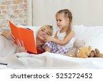 happy small girl lying in bed... | Shutterstock . vector #525272452