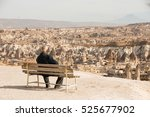 Small photo of Cappadocia, Turkey, November 12, 2016 a man sitting on a bench and admire the rocky landscape