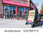 Small photo of Fairfax, Virginia - November 27, 2016: Noodles & Company World Kitchen outdoor seating area with Now Hiring sign