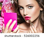 woman applying lipstick looking ... | Shutterstock . vector #526002256
