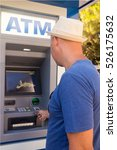 Man Using Atm To Withdraw Cash...
