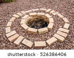 Small photo of Fire pit made of the yellow aluminous bricks surrounded by pebble in the autumn garden