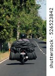 Small photo of Balinese Motorcyclist carrying an abnormal load of used tyres on the back of the bike