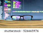 Stock photo eyeglasses in front off computer screen with code syntax 526665976