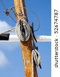 Ropes and mast details of a sailing boat against a blue sky - stock photo