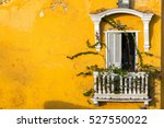 Old colonial balcony in a historic yellow building in Cartagena, Colombia