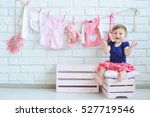 Stock photo portrait of a cute little smiling girl with baby clothes hanging on background 527719546