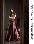 Small photo of Attractive woman in long claret lace dress. Reflected in mirror. Vintage