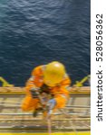 Small photo of Man working overboard. Abseiler climbing up at the edge of oil and gas rig platform in the middle of sea. Motion blur