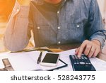 man counting using calculator... | Shutterstock . vector #528243775