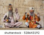 Small photo of Two hindu sadhu holy man, sits on the ghat, seeks alms on the street in Jaisalmer, Rajasthan, India. Close up