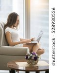 Small photo of Profile portrait of a young woman in a modern room, comfortable in her armchair with a laptop, business coaching, social media consultant, part-time contract worker, affiliate marketing. Lifestyle