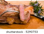 beef steak grilled with herbs on wooden table - stock photo