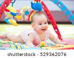 Sweet Baby Crawling And Playing With Toys On Carpet - stock photo