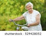 senior woman with bike in park. | Shutterstock . vector #529428052