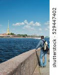 Small photo of ST. PETERSBURG, RUSSIA - JULY 11, 2016: Tourist admiring a view of the Peter and Paul Cathedral, St. Petersburg, Russia