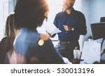Small photo of Hispanic businessman holding papers hands and smiling.Young team of coworkers making great business discussion in modern coworking office.Teamwork people concept.Horizontal, blurred background, flares