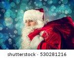 winking santa claus carries a... | Shutterstock . vector #530281216