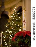 Small photo of Paschal Candle and poinsettia with lit Christmas tree in background (4666)