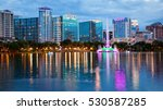 Orlando, Florida city skyline and water fountain at night in Lake Eola Park, building logos blurred for commercial use