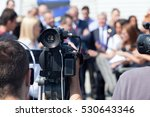 Small photo of Filming an media event with a video camera. Press conference.