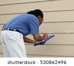 Small photo of Insurance adjuster records hail damage to siding