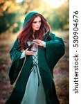 Small photo of Beautiful red haired girl in green medieval dress in a hood holding a sand glass and looking afar.Fairy tale story about brave heart woman.Warm art work