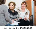 Small photo of account manager helping positive spanish elderly women with finances at home