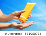 Small photo of Female hands with sun protection cream on sky background. Skin care concept.